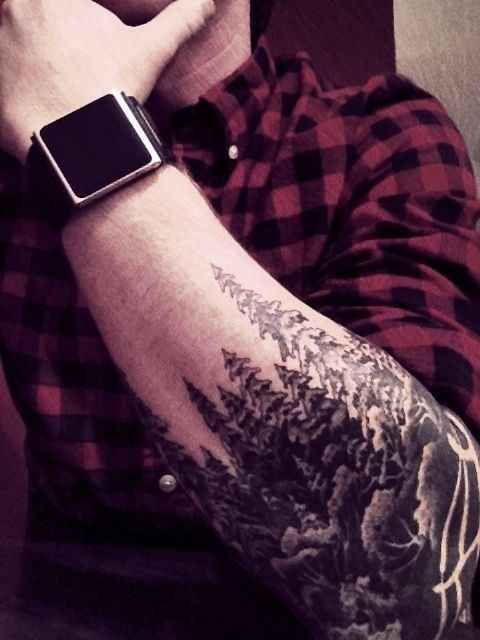 c8f2d7507 This woodland scene is a partial sleeve tattoo. It starts at the elbow and  the group of tall pine trees point toward the wrist. There is also a wooden  fence ...