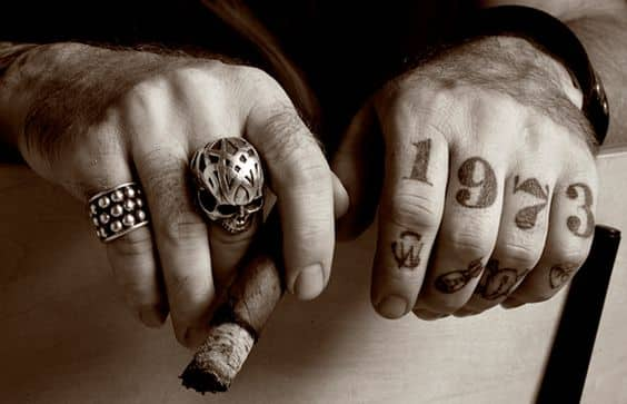 close up photo of tattooed hands holding cigar with big skull ring
