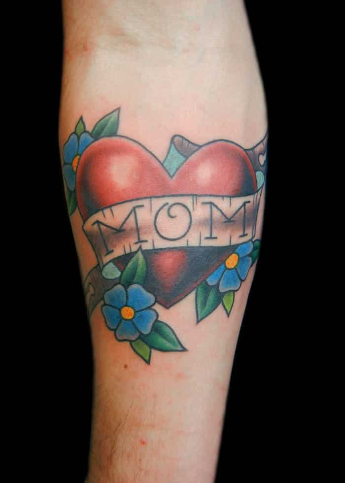 92ae44b58 A simple heart tattoo inked on the skin in loving memory of a mother.  Easily noted is the colorful nature of the design. Light blue inking for  the petals, ...